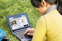 Looking over the shoulder of a woman with her hair back in a ponytail as she sits in the grass and works on her tablet