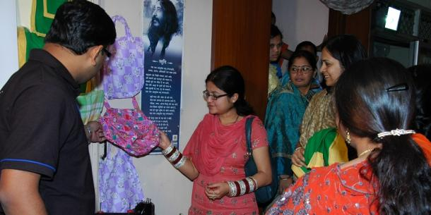 Indian women show examples of some bags they made