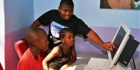 Three youth gather around a computer monitor