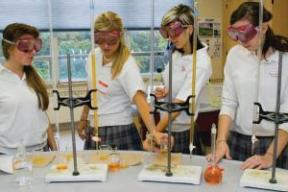 Four girls in a science lab setting wearing googles