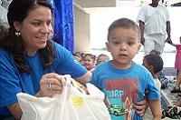 a woman intel volunteer holds a bag for a young toddler boy