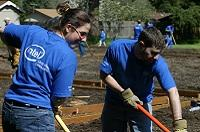 male and female Intel volunteers work with rakes and shovels