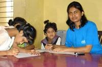 Intel volunteer in India works with 2 girls at a desk