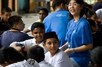 A female Intel volunteer in Malaysia works witn kids