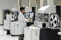 Staff at Intel in China work with large equipment in a lab