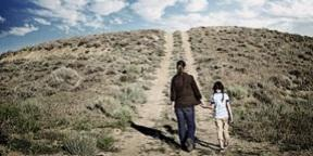 Woman and young girl walking uphill in desert terrain